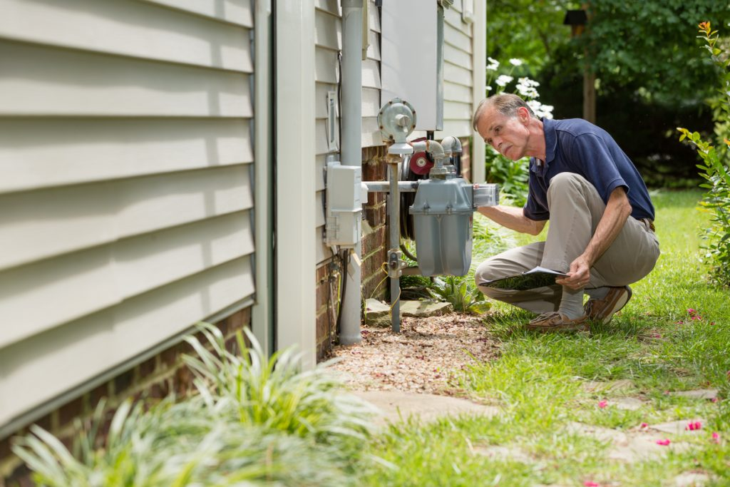Home inspector, outside, examines a residential natural gas meter.