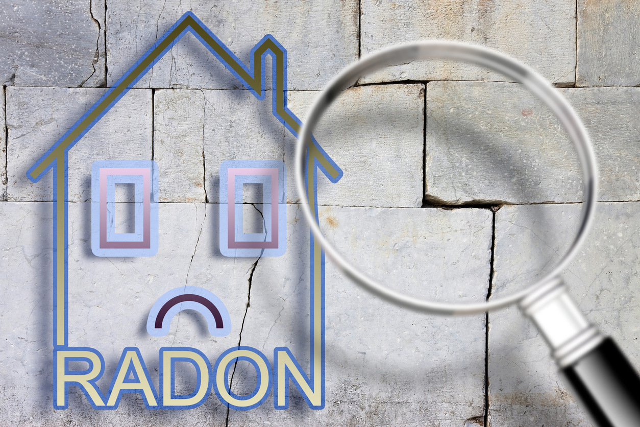 The danger of radon gas in our homes - concept image with an outline of a small house with radon text against a cracked stone wall with a magnifying glass